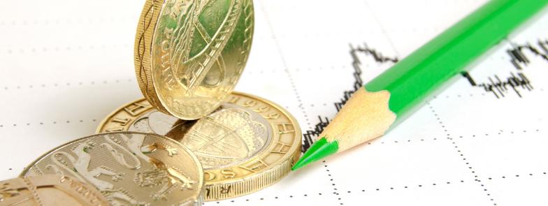 British Pound Coins alongside a pencil